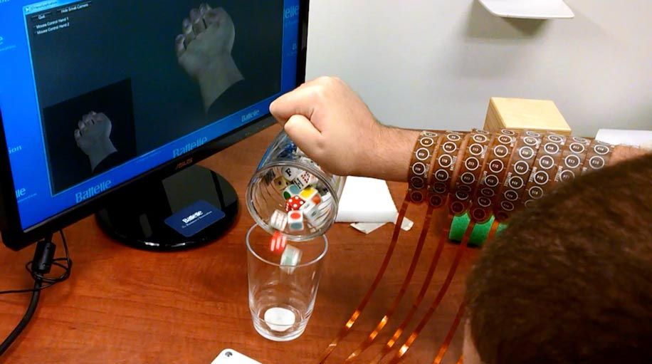 The computer screen in the upper right corner shows an avatar of Burkhart's hand in a clenched position, which is how his hand (middle of screen) is gripping the mug. He is pouring cubes from the mug into a glass.