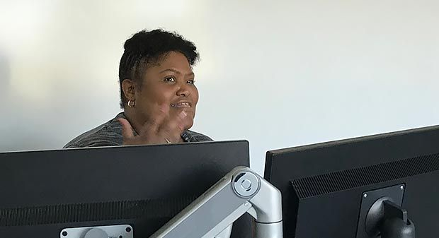 Louvere Walker-Hannon sitting at a desk with two monitors, while speaking and gesturing with one hand.