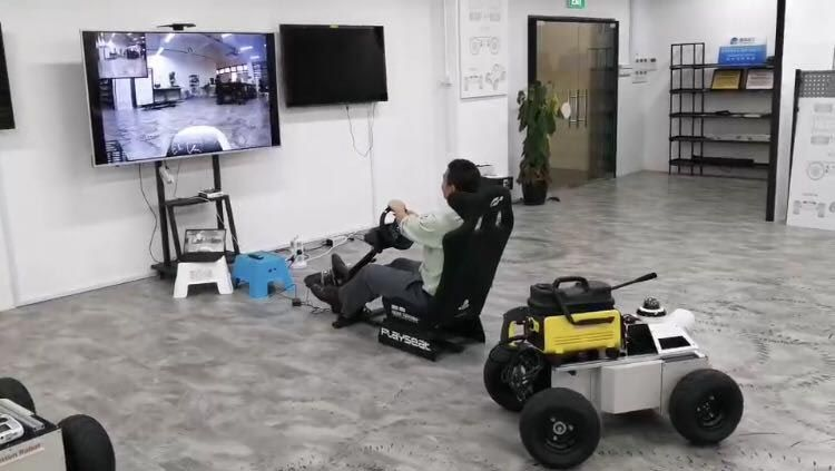 The robot is shown in the foreground. An operator is seated in front of a large screen that shows the robot's surroundings.  The operator is controlling the robot with a steering wheel.